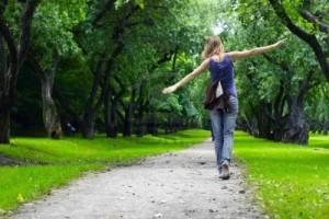 7888887-woman-walking-on-path-in-green-summer-park