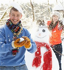 Adults playing in snow with snowman
